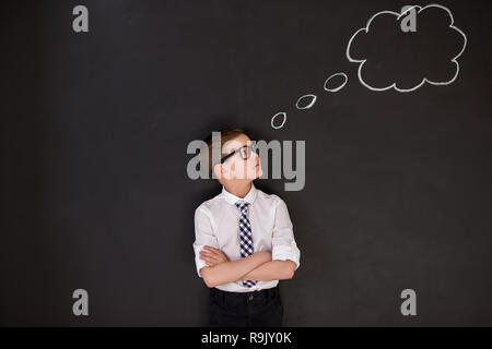 Handsome school boy in googles white shirt tie standing close to school desk with thinking cloud above the head - Stock Photo