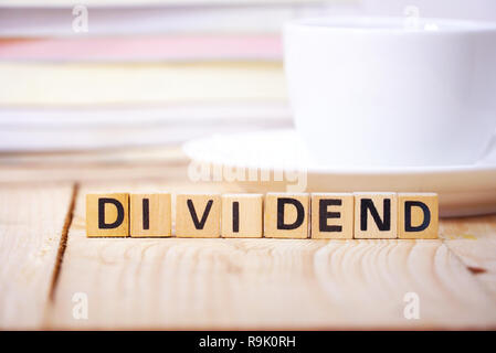 Text ' DIVIDEND 'on cube dice on working table , finance concept. - Stock Photo