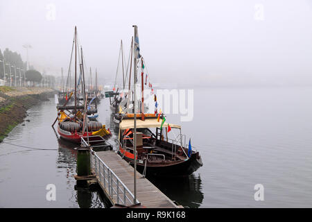Porto, Portugal - August 18, 2013: Traditional Rabelo Boats of the River Douro, anchored in a pier of Gaia, twin city of Porto, in a foggy morning - Stock Photo