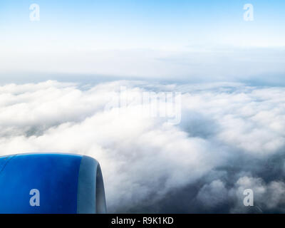 view of airplane engine over dense gray clouds in blue sky during flight through porthole - Stock Photo