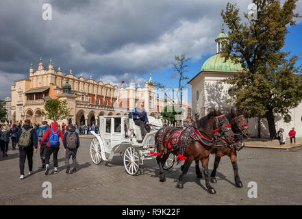 Poland, city of Krakow, horse carriage ride, sightseeing tour around the Old Town Main Market Square, Cloth Hall and St Adalbert Church in the backgro - Stock Photo