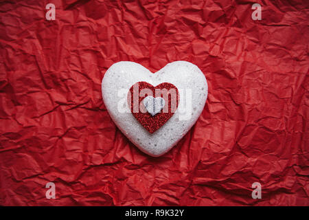 Heart on a red background. Concept for Valentine's Day or Women's Day or the topic of health, life, donation and help. In minimal style. - Stock Photo
