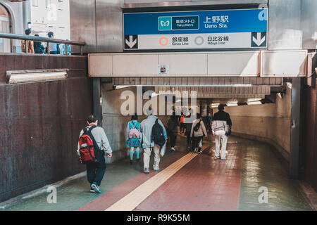People entering Ueno subway station through entrance carrying their backpack - Stock Photo