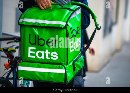 Uber Eats is an American online food ordering and delivery service. Delivery in progress on Vienna street. Austria. - Stock Photo