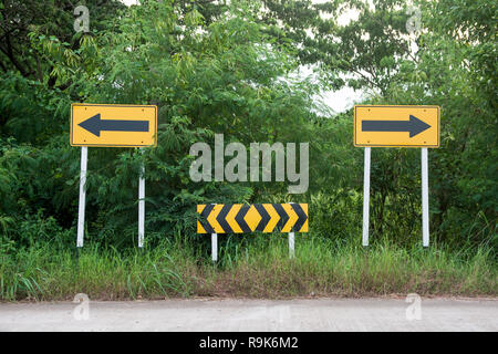 Road sign. Yellow arrow signs at the end of the road pointing left and right - Stock Photo