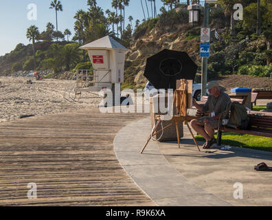 Laguna Beach, California - October 9, 2018: Artist paints beach scene while sitting on a bench by the boardwalk and beach on a beautiful sunny day in  - Stock Photo