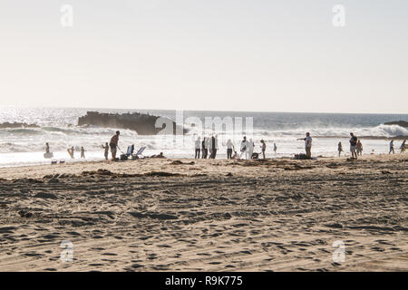Laguna Beach, California - October 9, 2018: Group of people standing on a hazy beach, some in bathing suits but many in shorts and shirts - Stock Photo