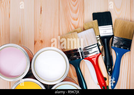 Four open cans of paint with brushes on natural wooden background. Yellow, white, pink, turquoise colors. Renovation concept.
