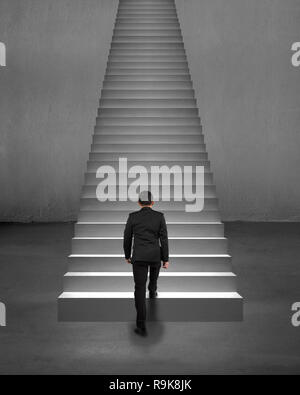 Rear view businessman climbing on stairs with spot lighting and concrete background - Stock Photo