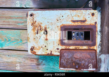 An old and rusty electric circuit breaker placed on a wall in a rusty metal box - Stock Photo