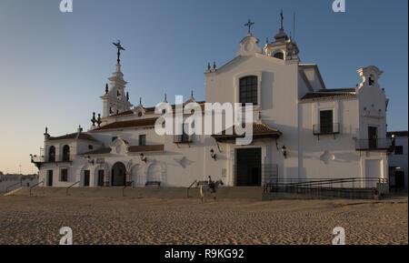 A man on a horse is praying in front of the Ermita de El Rocio church at the end of the day, El Rocio, Spain - Stock Photo