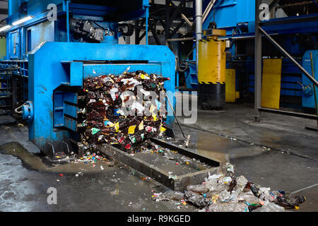Modern waste sorting and recycling plant, hydraulic press makes wired bale from pressed PET bottles for processing and reuse of plastic. Concept of de - Stock Photo
