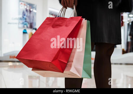 Close up of colorful paper bags in woman's hands on shopping centre background. Woman in skirt and black tights standing in mall passing area and hold - Stock Photo