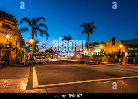 Intersection on Main Street in downtown Ventura, California, USA decorated with Christmas lights and streaking traffic headlamps has open restaurants  - Stock Photo