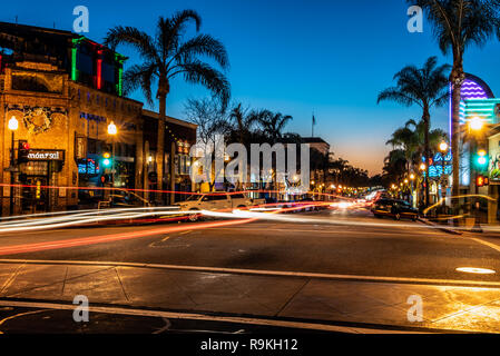 Intersection on Main Street in downtown Ventura, California, USA decorated with Christmas lights and long line of vehicles has open restaurants on Chr - Stock Photo