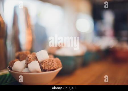 Brown sugar cubes in a ceramic dish - Stock Photo