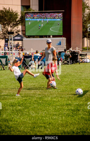 While a daytime audience watches a World Cup soccer game on a giant outdoor television screen in Costa Mesa, CA, a mother plays the game with her children on a nearby field. - Stock Photo