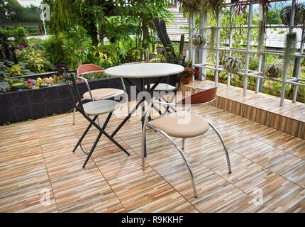 Landscaping with table set in garden with plants and trees background - Stock Photo