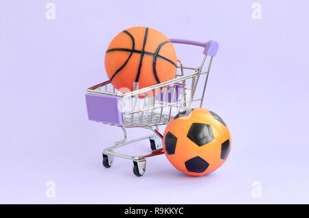 Orange basketball and soccer ball in shopping cart on violet. The concept of selling sports equipment, predictions for sports matches, sports betting - Stock Photo