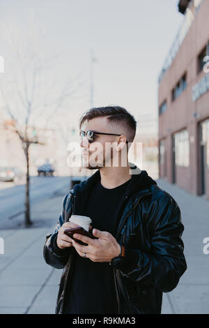 Young Happy Millennial Male Business Man Entrepreneur in Urban Downtown Metropolis on His Cell Phone Texting and Taking Business Phone Calls, Coffee - Stock Photo