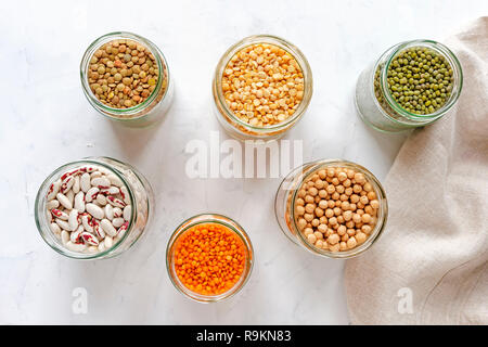 Open glass jars full of assorted dried legumes with mung beans, beans, lentils and peas over a white background - Stock Photo