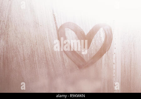 A heart-shaped drawing drawn by a finger on a misted glass in rainy weather - Stock Photo