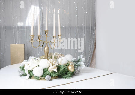 New Year's decorations and a golden candlestick with burning candles stand on the surface of a white grand piano - Stock Photo
