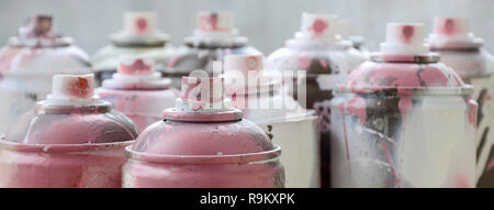 A lot of dirty and used aerosol cans of bright pink paint. Macro photograph with shallow depth of field. Selective focus on the spray nozzle - Stock Photo