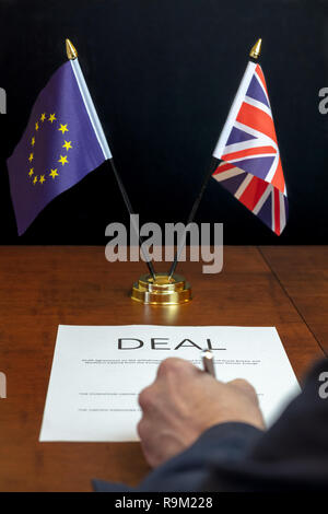 Brexit Concept. Male Hand From Rear Signing Sheet of Paper Headed 'Deal' on a Desk With Table top UK and EU Flags Behind - Stock Photo
