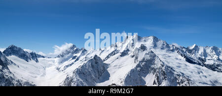 Panorama of snow-capped mountain peaks and beautiful blue sky with clouds at sun windy day. Caucasus Mountains in winter, region Dombay. - Stock Photo