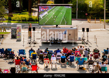 A daytime audience watches a World Cup soccer game on a giant outdoor television screen in Costa Mesa, CA. - Stock Photo