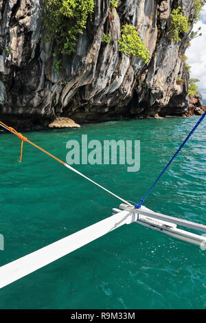 Green water-outrigger rigging of Filipino bangka tour boat facing Pinasil island's Cathedral Cave-interior lit some times of day by sun coming through - Stock Photo
