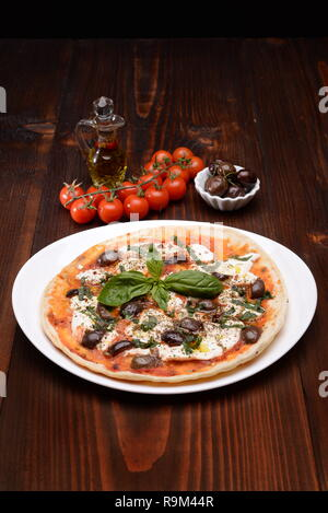 Dish with cottage cheese Piadina olives and basil in the table - Stock Photo