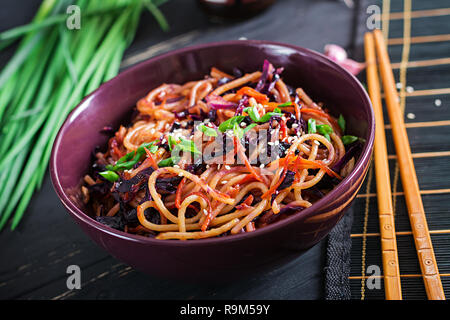 Chinese food. Vegan stir fry noodles with red cabbage and carrot in a bowl on a black wooden background. Asian cuisine meal.