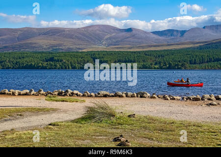 Loch Morlich and Cairngorms in Glenmore Cairngorms National Park Highland Scotland with canoeists and ducks with Cairngorm mountain behind