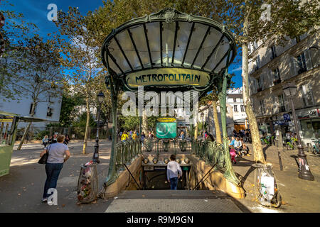 People entering and leaving Abbesses Metro Station in Montmartre Paris. The station's glass covered entrance or édicule was designed by Hector Guimard - Stock Photo