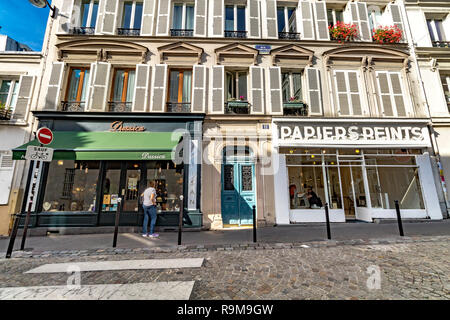 Shops and boutiques along Rue La Vieuville , a cobbled street in  Montmartre , with white shutters on the windows of the apartments above the shops - Stock Photo