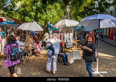 Visitors and tourists watch artists painting and displaying their work in Place Du Tetre , Montmartre Paris - Stock Photo