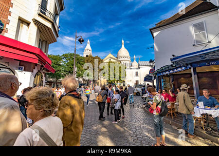 Visitors and tourists in Place Du Tetre , Montmartre Paris with The Sacre Coeur in the distance,Paris , France - Stock Photo