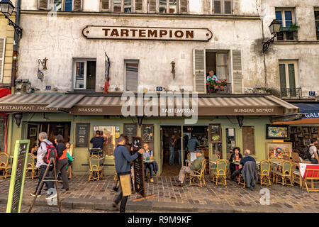 A man looking through the window out onto the street from above Tartempion a restaurant in Montmartre busy with people sitting outside,Montmartre - Stock Photo