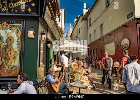 A man sitting playing a guitar outside de La Bonne Franquette, a cafe,  restaurant  ,whilst  people enjoy lunch in the sunshine ,Montmartre, Paris - Stock Photo