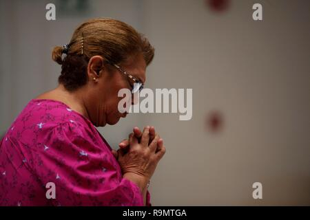 Panama City, Panama. 26th Dec, 2018. A woman prays in front of the Pilgrim Cross of the World Youth Day and the Byzantine Icon of the Virgin Mary 'Salus Populi Romani' (Protector of the Roman People) in the parish of Our Lady of Guadalupe, in Panama City, Panama, 26 December 2018. The National Government announced today the three-day closure of public offices in Panama City to help the mobility of the more than 500,000 pilgrims expected to attend the World Youth Day 2019 which will be held from 22 to 27 January in the Panamanian capital. Credit: Bienvenido Velasco/EFE/Alamy Live News - Stock Photo