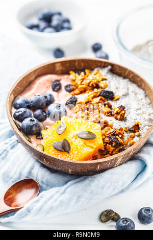 Vegan smoothie bowl with chia pudding, berries and granola in a coconut shell on a white wooden background. Plant based diet concept. - Stock Photo