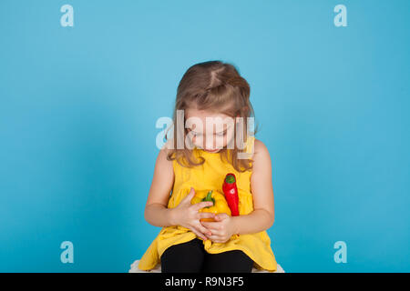 little girl with red bell pepper with fresh vegetables - Stock Photo