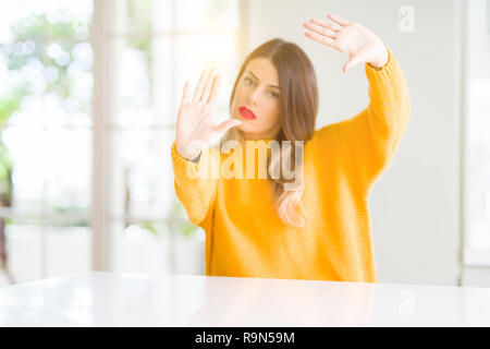 Young beautiful woman wearing winter sweater at home Smiling doing frame using hands palms and fingers, camera perspective - Stock Photo
