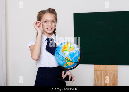 girl school girl in glasses at the blackboard on the lesson at school - Stock Photo