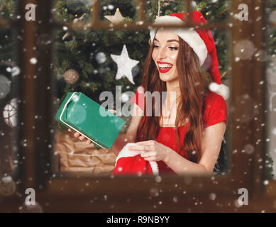 e02557538aa0a ... Excited christmas woman wearing Santa hat and red dress sitting near the  New Year spruce and