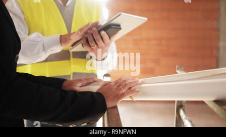 Men and woman meeting in construction site. Teamwork with foreman speaking with engineer holding blueprints. Focus on wedding ring on female's hand. C - Stock Photo