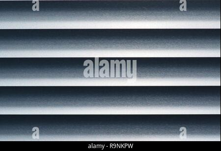 Abstract of monochrome metal blinds with a straight horizontal view, showing contrasting highlights and shadows. - Stock Photo