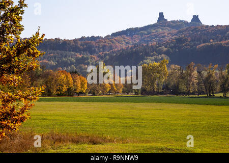 Autumn landscape in Bohemia dominating the ruins of a medieval castle on a hill and high rock. Historical landmark of the Czech Republic and a popular - Stock Photo